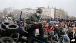 Người biểu tình thân Nga đeo mặt nạ bảo vệ các rào chắn tại tòa nhà chính quyền khu vực ở Donetsk, Ukraine.