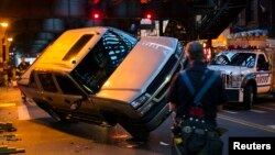 New York Fire Department officers watch as New York Police Department (NYPD) officers work to right a truck that had flipped on its side in an accident in New York, April 26, 2013.