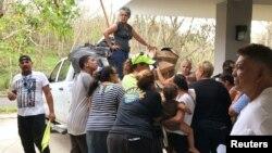 Residentes desplazados por el huracán María en Guaynabo, Puerto Rico se reúnen en torno a un vehículo con suministros, el 1 de octubre de 2017.