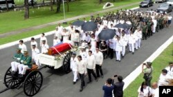 In this photo provided by the Office of Ilocos Norte Governor Imee Marcos, Imelda Marcos, in black on a wheelchair under an umbrella, the widow of the late dictator Ferdinand Marcos, and their close relatives follow the flag-draped casket of Ferdinand Marcos, and their close relatives follow the flag-draped casket of Ferdinand Marcos during a ceremony of his burial at the Heroes' Cemetery in suburban Taguig city, Philippines, Nov. 18, 2016.