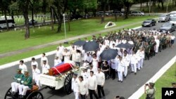 Imelda Marcos (mengenakan baju hitam di atas kursi roda, di bawah payung), janda mantan diktator Filipina Ferdinand Marcos, dan keluarga dekat mereka ikut dalam iring-iringan peti yang membawa jenazah Ferdinand Marcos yang akan dimakamkan di Taman Makam Pahlawan di kota Taguig, Filipina (18/11).