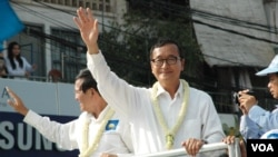 FILE - Opposition leader Sam Rainsy (white shirt, right), and deputy opposition leader Kem Sokha (left) wave to people watching the march, Phnom Penh, Cambodia. (Robert Carmichael/VOA).