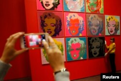 """An employee poses with 10 screenprints of Marilyn Monroe by Andy Warhol as part of the exhibition""""American Dream: pop to the present"""" at the British Museum in London, Britain, Feb. 10, 2017."""
