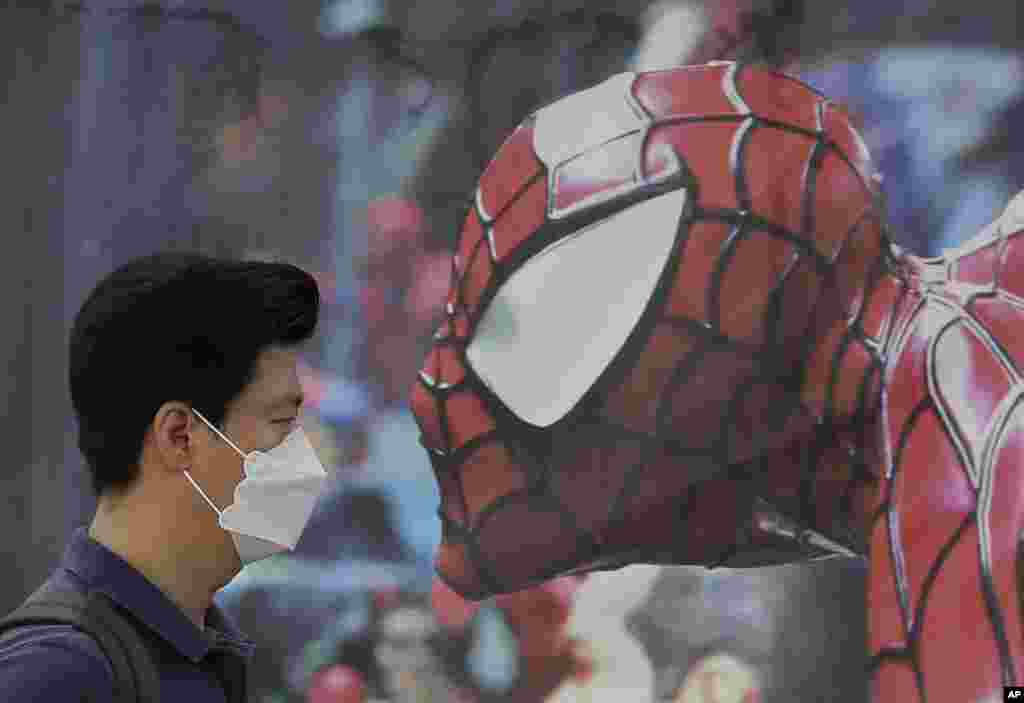 A man wearing a mask as a precaution against the Middle East Respiratory Syndrome (MERS) virus walks by a Spiderman poster in Seoul, South Korea.
