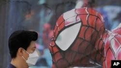 បុរសជនជាតិកូរ៉េខាងត្បូង ពាក់ម៉ាស់ការពារមេរោគ MERS ដើរនៅក្បែររូបពាណិជ្ជកម្ម Spider-Man នៅទីក្រុងសេអ៊ូល ប្រទេសកូរ៉េខាងត្បូង កាលពីថ្ងៃទី១០ ខែមិថុនា ឆ្នាំ២០១៥។