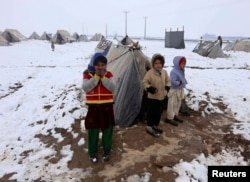 FILE - Internally displaced Afghan children stand outside their shelter in the cold at a refugee camp on the outskirts of Herat city, Afghanistan.