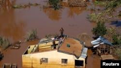 Um homem em cima de uma casa numa área completamente inundada, depois da passagem do ciclone Idai. Distrito de Buzi, Beira, Moçambique, 22 de Março, 2019.