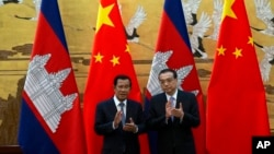 Cambodian Prime Minister Hun Sen, left, applauds with Chinese Premier Li Keqiang during a signing ceremony at the Great Hall of the People in Beijing, China, Tuesday, Jan. 22, 2019. (AP Photo/Ng Han Guan, Pool)