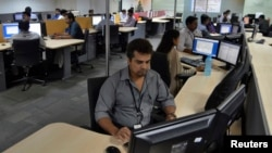 FILE - Employees of ISGN work at their stations inside the company headquarters in the southern Indian city of Bangalore.