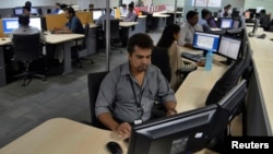 FILE - Employees of ISGN work at their stations inside the company headquarters in the southern Indian city of Bangalore, India.