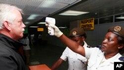 20일 나이지리아 라고스 국제공항에서 보건 관계자들이 에볼라 감염 여부를 조사하기 위해 승객들의 체온을 재고 있다.