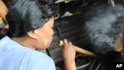 FILE - Fuel-efficient stoves use significantly less firewood than a traditional three-stone stove. This woman in Burma is using a pipe to help increase the fire's flames to cook the food.