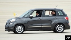 FILE - Pope Francis waves from inside a Fiat 500L as he departs Andrews Air Force Base in Maryland, Sept. 22, 2015. One of the two Fiats used by Pope Francis during his visit to Philadelphia last year is going up for auction.
