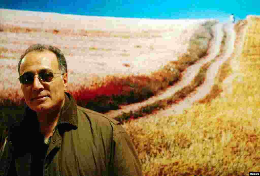 """کیارستمی در کنار پوستر فیلم """"باد ما را خواهد برد"""" که در سال ۱۹۹۹ ساخته شد."""
