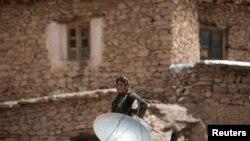 Perempuan Iran berdiri di belakang parabola di atap rumahnya di desa Palangan. (Foto: ilustrasi)