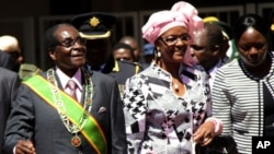 """Zimbabwe President Robert Mugabe, left, and his wife Grace, arrive for celebrations to mark 32 years of independence of Zimbabwe, in Harare, Wednesday, April 18, 2012. In an address, Mugabe said that political violence must be """"buried in the past"""" to move"""