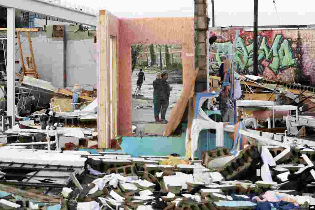 People are seen in a mirror of a building destroyed by overnight storms in Nashville, Tennessee.