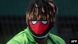 Bénévole du Plan de solidarité du Panama portant un masque alors qu'il livre de la nourriture aux familles à faible revenu du quartier El Chorrillo de Panama City en période de pandémie de coronavirus, 1er avril 2020. (Photo Luis Acosta/AFP)