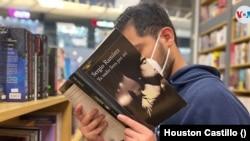 Un hombre hojea un libro del escritor Sergio Ramírez en una librería en Managua, Nicaragua. Foto Houston Castillo, VOA.
