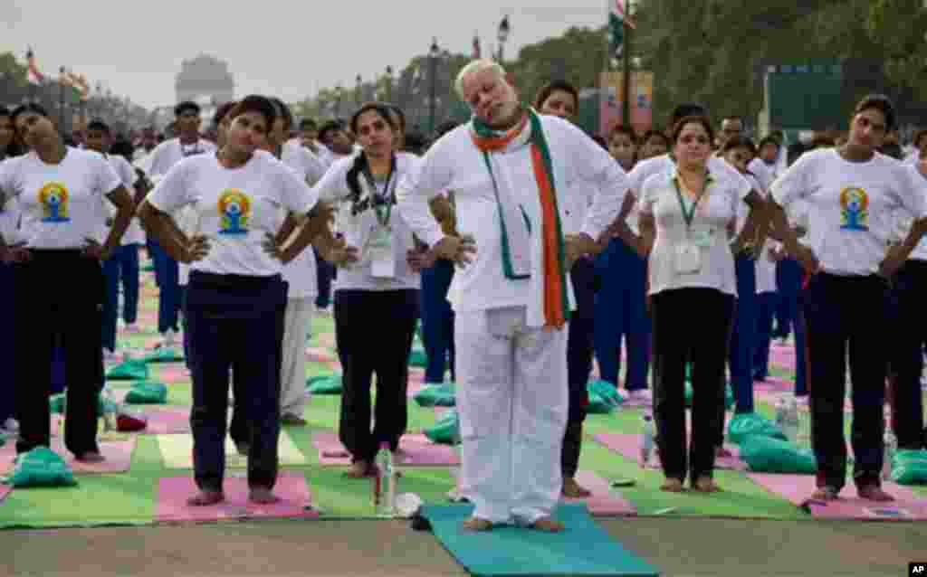 Indian Prime Minister Narendra Modi performs yoga along with thousands of Indians on Rajpath, in New Delhi, India, Sunday, June 21, 2015. Millions of yoga enthusiasts are bending their bodies in complex postures across India as they take part in a mass yo