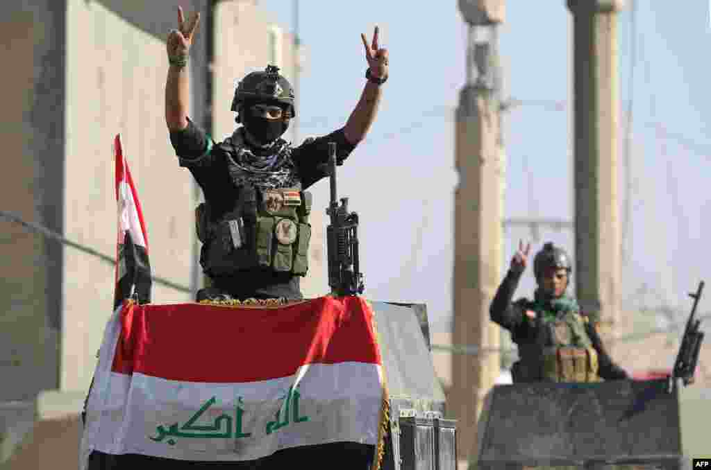 "Members of Iraq's elite counterterrorism service flash the ""V"" for victory sign in the city of Ramadi, the capital of Iraq's Anbar province, about 110 kilometers west of Baghdad, after recapturing it from the Islamic State jihadist group."