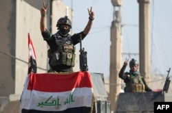 "Members of Iraq's elite counter-terrorism service flash the ""V"" for victory sign, Dec. 29, 2015 in the city of Ramadi, the capital of Iraq's Anbar province, about 110 kilometers west of Baghdad, after Iraqi forces recaptured it from the Islamic State (IS)."