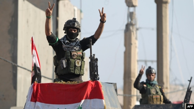 "Members of Iraq's elite counter-terrorism service flash the ""V"" for victory sign, Dec. 29, 2015, in the city of Ramadi, the capital of Iraq's Anbar province, about 110 kilometers west of Baghdad, after Iraqi forces recaptured it from the Islamic State group."