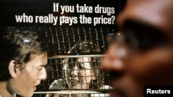FILE - Human rights lawyer M. Ravi stands in front of a drug prevention advertisement outside the Singapore Changi Prison, Jan. 25, 2007.