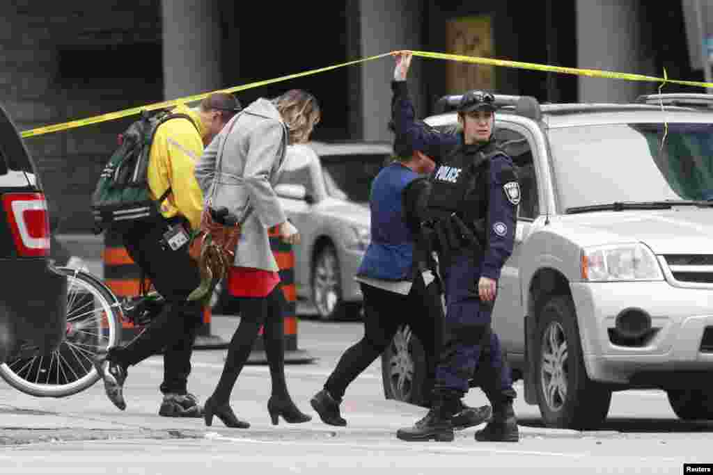 A police officer holds up a length of police tape for pedestrians leaving the downtown area following shooting incidents in Ottawa.