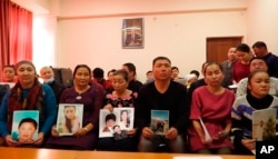 In this Dec. 7, 2018, image made from video, relatives of people missing in China's far western region of Xinjiang hold up photos at an office of a Chinese Kazakh advocacy organization in Almaty, Kazakhstan.