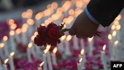 19일 파키스탄 이슬라마바드 의회 앞에 설치된 탈레반 학교 공격 희생자 기념 묘지에 한 의원이 꽃을 놓고 있다.