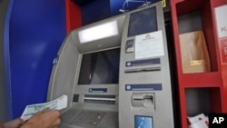A man uses an ATM machine at KBZ bank's head office in Rangoon, March 14, 2012.