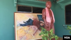 A statue of Kem Ley is displayed in front of a painting that depicts the scene of his death at Caltex station last year, Takeo province, Cambodia, July 02, 2017. (Hul Reaksmey/VOA Khmer)