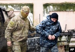 FILE - A Ukrainian sailor seized by Russia, right, is escorted by a Russian intelligence officer to a court room in Simferopol, in Russia-annexed Crimea, Nov. 27, 2018.