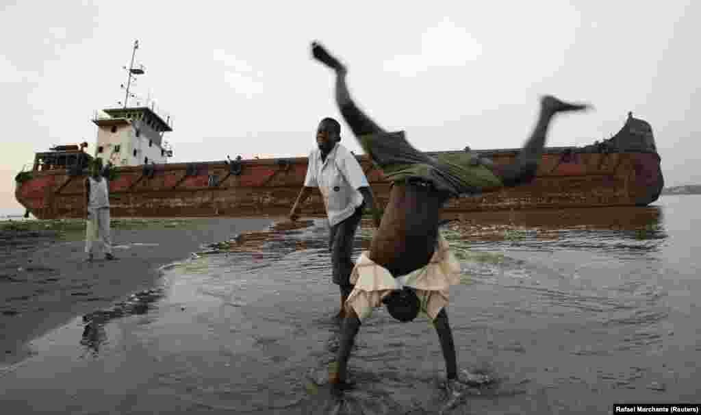 Uma criança em acrobacias na praia dos pescadores em Cabinda