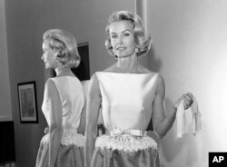 FILE - In this April 6, 1962, photo, socialite-actress Dina Merrill models the gown she was to wear at the Academy Awards presentation in Los Angeles. Merrill, the rebellious heiress who defied her super-rich parents to become an actress, died May 22, 2017, at age 93.