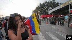 Una mujer llora en las afueras del hospital militar donde murió Chávez. Los restos del ex mandatario serán trasladados a la Academia Militar.