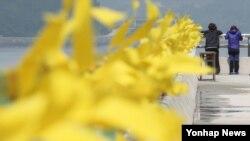 세월호 침몰 사고 36일째인 21일 오전 전남 진도군 팽목항에서 실종자 가족들이 바다를 바라보고 있다. 난간에는 희생자들을 추모하는 노란 리본이 매어져있다.