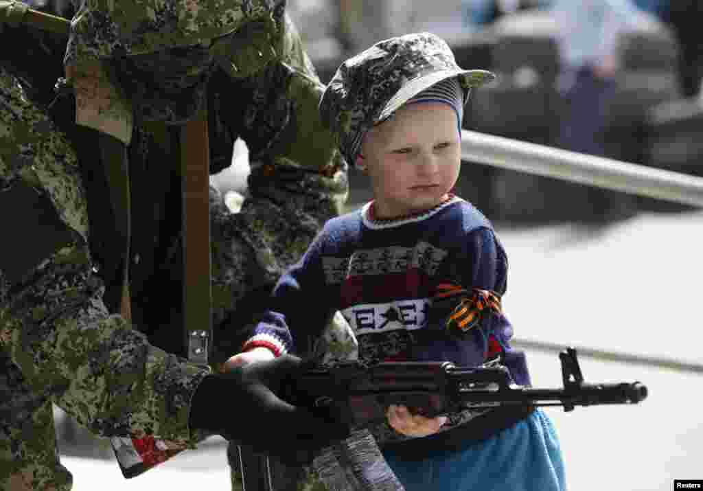 A pro-Russian armed man hands his weapon to a boy posing for a picture for his father in front of the seized town administration building in Kostyantynivka, April 28, 2014.