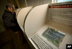 A Chinese investor uses a computer terminal to check stock prices in a brokerage house in Beijing, Jan. 29, 2016.