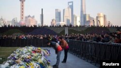 People bow during a memorial ceremony for people who were killed in a stampede incident during a New Year's celebration on the Bund, in Shanghai, Jan. 2, 2015.