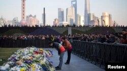 Người dân cúi mình trong lễ tưởng niệm các nạn nhân của vụ giẫm đạp ở Bến Thượng Hải , 2/1/2015.