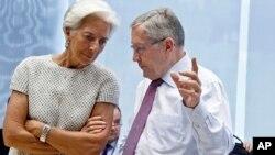 ຫົວໜ້າຜູ້ອຳນວຍການ ອົງການກອງທຶນສາກົນ ທ່ານນາງ Christine Lagarde ໂອ້ລົມກັບ ທ່ານ Klaus Regling, ປະທານຂອງ ຫ້ອງການສະຖຽນລະພາບ ດ້ານການເງິນ ຢູໂຣບ ໃນລະຫວ່າງກອງປະຊຸມ ບັນດາລັດຖະມົນຕີ ການເງິນ ເຂດໃຊ້ເງິນຢູໂຣ ທີ່ອາຄານ EU Lex ໃນນະຄອນ Brussels, ວັນທີ 11 ກໍລະກົດ 2015.