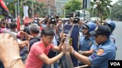 Người biểu tình xô đẩy cảnh sát để đến gần Tòa Đại sứ Hoa Kỳ trong thủ đô Manila trước chuyến đến thăm của Tổng thống Obama, 23/4/14
