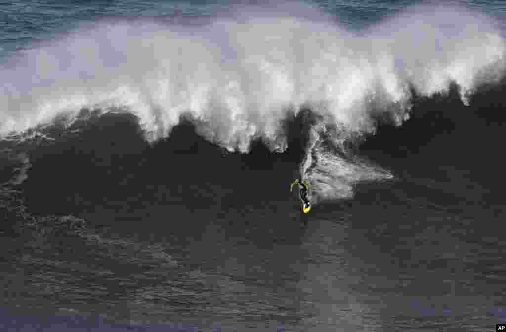 Peselancar AS Garrett McNamara menari di atas ombak di pantai Praia do Norte di Nazare, Portugis (29/1).