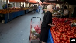 FILE - A elderly woman shops in Athens on July 3, 2015. Europe is the continent most affected by an aging population, and Spain has recorded more deaths than births in the first half of 2015.