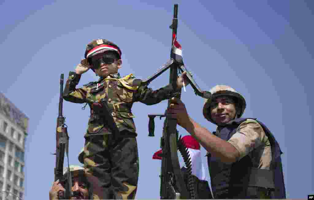 An Egyptian boy in an army costume salutes while posing next to army soldiers, from atop an armored vehicle guarding an entrance to Tahrir Square, Cairo, Oct. 6, 2013.