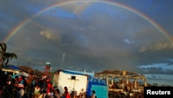 A rainbow appears above Typhoon Haiyan survivors at the Tacloban airport.