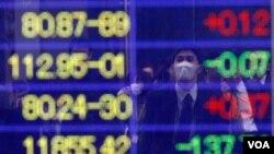 Seorang pria mengamati angka-angka indeks Nikkei pada sebuah layar di Tokyo, Kamis (17/3). Indeks Nikkei naik 5,7 persen yang memulihkan hampir sepertiga penurunan sebelumnya pekan ini.
