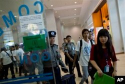 A group of former slave fishermen escorted by Myanmar police officers and IMO officials arrive at Myanmar's international airport, Yangon, Saturday, May 9, 2015. They were the first Burmese men to return home following an Associated Press investigation.